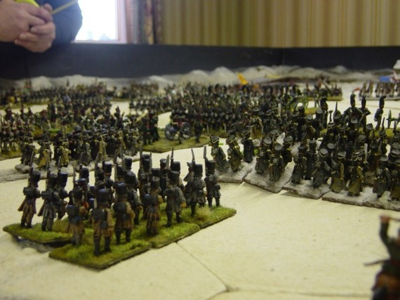 Kulniev's Brigade attacks. In the foreground, the St Petersburg Militia march behind the Navajinski  Infanty regiment. The brigade artillery pounds at  the French right. When the order changes from  ENGAGE to ASSAULT, two battalions of Jagers  attack in massed columns on the extreme right of  the French line. The attack looks promising but it  falls into disorder, because the columns are too  close to each other. They cannot get to grips with  the enemy. The assault grinds to a halt.
